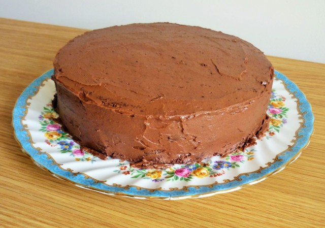Chocolate fudge cake with a smooth layer of chocolate buttercream before final decorations