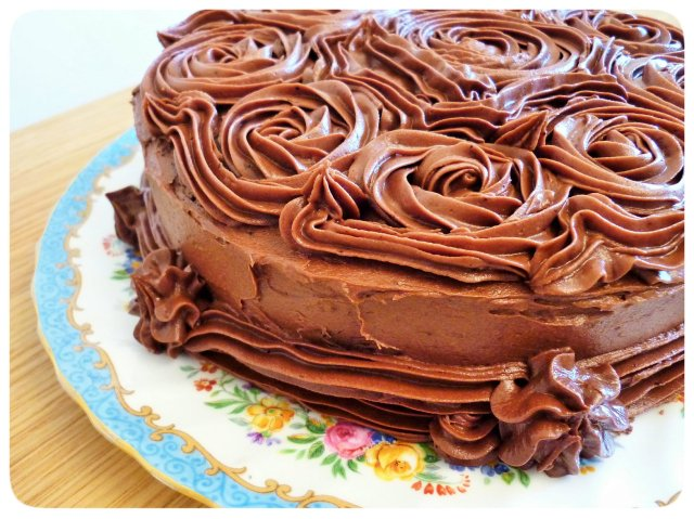 Chocolate fudge cake with chocolate buttercream frosting close up on rosettes