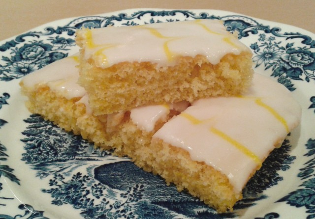 Lemon sponge cake with white icing and yellow feathered icing sliced 3