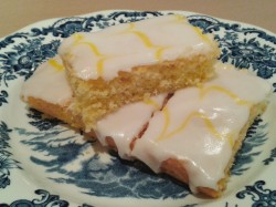 Lemon sponge cake with white icing and yellow feathered icing sliced