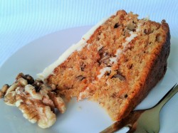 Slice of carrot cake with cream cheese frosting and walnuts