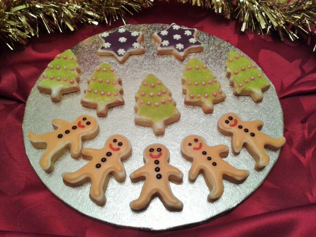 Christmas biscuits cookies gingerbread men, green sparkly trees and stars with snowflakes
