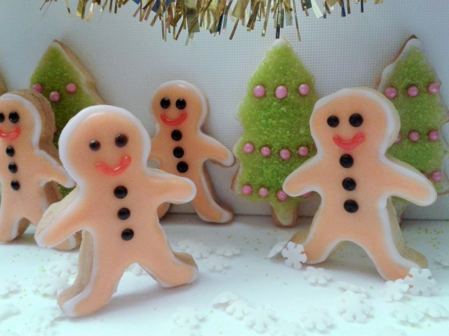 Mini gingerbread men biscuits cookies with Christmas tree cookies with green sugar sparkle decorations