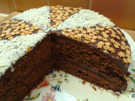 Heavenly chocolate cake with fudge frosting white chocolate shavings and gold sugar stars cut