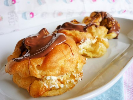 Giant choux buns profiteroles filled with double whipped cream and topped with melted Terry's chocolate orange