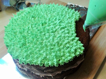 Chocolate easter and spring cake. Two layer sandwich cake with chocolate buttercream filling and grass effect topping. Piping in progress