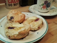 Freshly-baked cherry scones with hot butter and tea