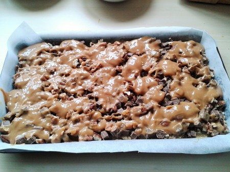 Oat and pecan squares with caramel and chocolate making stage 2