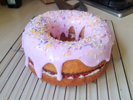 Giant doughnut cake with pink icing and hundreds and thousands