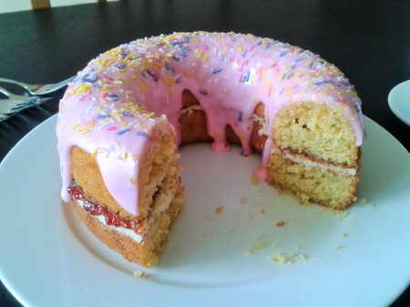 Giant doughnut cake with pink icing and sprinkles filled with jam and cream sliced
