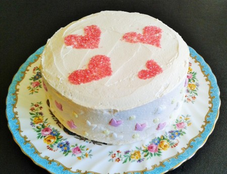 White chocolate layer cake with raspberry buttercream filling easy to slice ideal party cake with heart decorations
