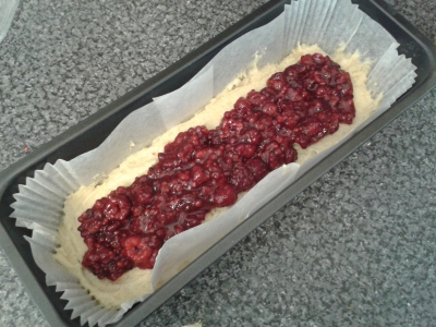 Layering raspberries in raspberry and walnut loaf cake easy cake recipe using raspberries