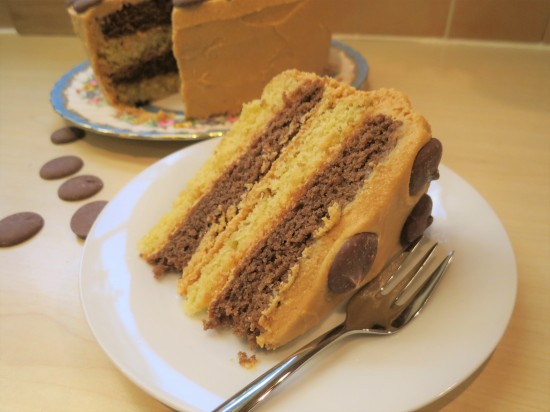 Easy chocolate vanilla and caramel layer cake with caramel buttercream frosting and chocolate caramel buttons uk slice simple recipe
