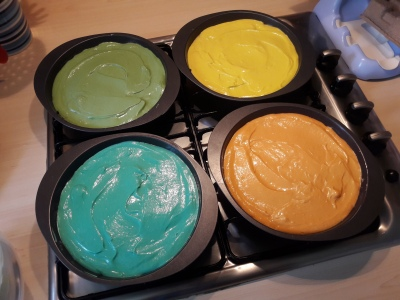 Four baking tins containing different colour spong cake mixture for rainbow layer cake ready to go in the oven