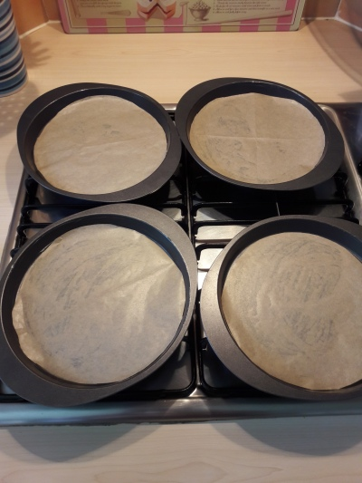 Image of four shallow circular tins lined and ready to use to make rainbow layer sponge cake