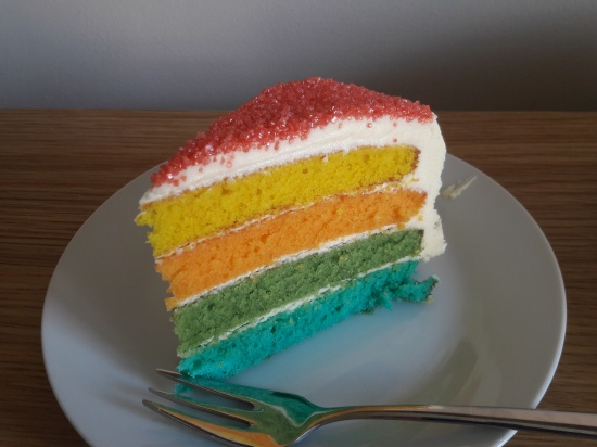 Picture of a slice of rainbow multicoloured layer sponge cake with white buttercream icing and red sprinkles
